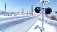 Wide shot woman and two men walking on skyrunners across railroad crossing