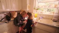 wide shot woman buttoning girl's sweater, kissing her / taking purse from kitchen counter + leaving with girl