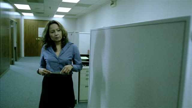 Wide shot woman distributing paychecks to office workers in cubicles / man opening paycheck in cubicle
