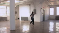 Wide shot woman entering empty loft space, looking around, and walking toward window/ Brooklyn, New York