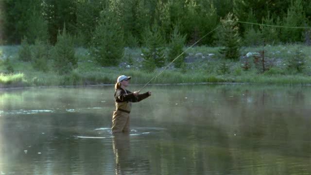 Wide shot woman fly fishing in river / Idaho