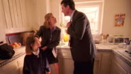 wide shot woman getting girl ready for school in kitchen / man comes in, kisses woman + leaves with girl