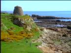 wide shot woman highland dancing by bagpiper on grassy coastal landscape / Scotland