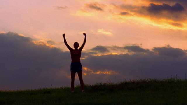 Wide shot woman jumping and raising arms in victory on field at dusk / Vermont