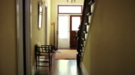 Wide shot woman leaving hallway out front door of house/ Roxbury, New York