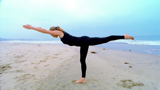 Wide shot woman performing 'mountain' yoga pose on beach / Los Angeles