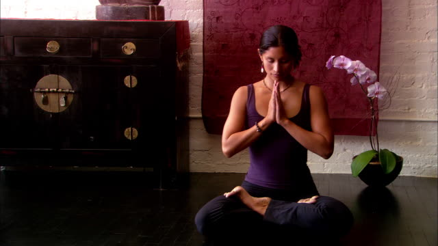 Wide shot woman sitting in lotus position and bringing hands together in prayer position