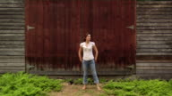 Wide shot woman standing in front of barn