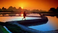 Wide shot worker walking along rice paddy and carrying farm tool with orange sun, hills in background / Yang-shu, China