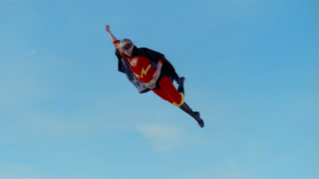 Wide shot young blonde woman in mask, cape, and superhero costume in midair simulating flying backwards after jumping on trampoline