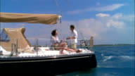 Wide shot Young couple relaxing on sailboat deck/ Harbor Island, Bahamas