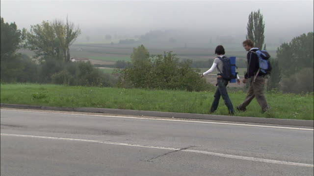 Wide shot young couple wearing backpacks hitchiking on roadside / running after car