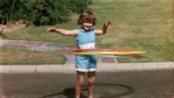 1958 wide shot young girl in blue jumpsuit hula hooping with three hula hoops on street