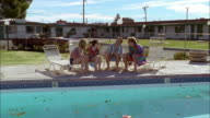 Wide shot young men and women sitting in beach towels + talking by motel swimming pool