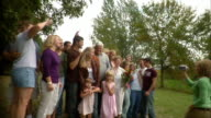 Wide shot Young woman filming large group of people at family reunion/ Oshkosh, Wisconsin, USA