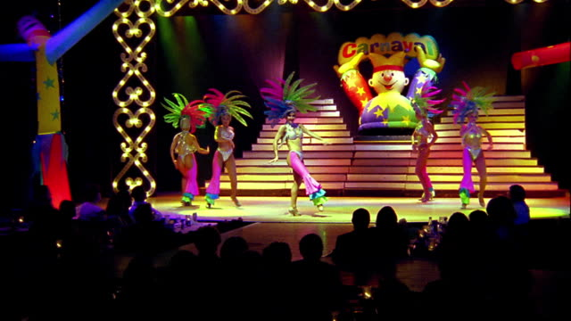 wide shot zoom in five female dancers in costume performing on stage / audience in foreground