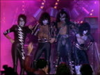 1982 wide shot zoom in Gene Simmons Paul Stanley and Kiss members posing on stage in costume makeup / AUDIO