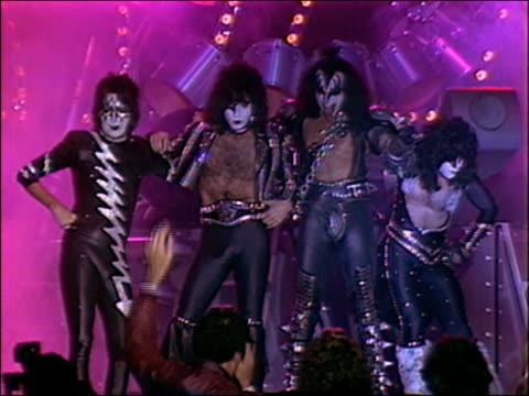 1982 wide shot zoom in Gene Simmons Paul Stanley and Kiss members posing on stage in costume makeup / AUDIO