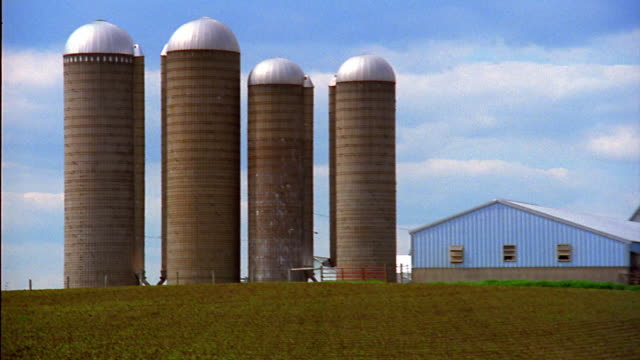 Wide shot zoom in pan from silos to farm buildings with cultivated fields in foreground / Iowa