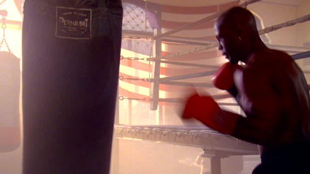 wide shot zoom in shirtless Black male boxer sparring with heavy punching bag in sunlit gym with American flag in background