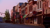 wide shot zoom in small town street with storefronts + road signs / Mississippi