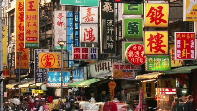 Wide shot zoom out time lapse people and traffic moving under signage on Snake Alley (Xi Yuan Road) / Taipei, Taiwan