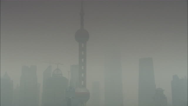 Wide Shot zoom-out - A haze shrouds the Shanghai Oriental Pearl TV Tower beside the Huangpu River./Shanghai, China