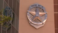 Wide Shot zoom-out - A sign in the shape of a badge denotes a police building. / USA