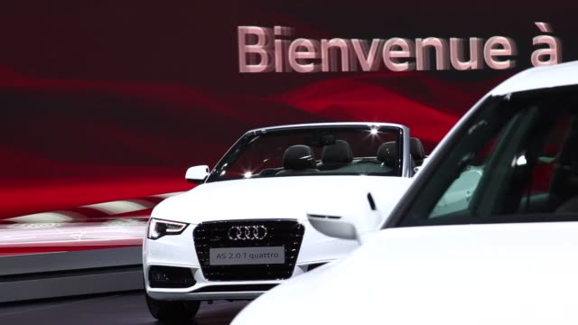 Wide shots of a yellow Audi model vehicle on display at the 2014 Geneva Auto Show in Palexpo Geneva Switzerland as security personnel usher visitors...