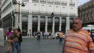 Wide shots pedestrians and taxi cabs pass Apple Incs new Spanish flagship store on Puerta de Sol square the day before opening to the public in...