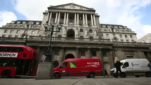 Wide shots pedestrians and traffic pass the Bank of England headquarters in London UK on Tuesday Feb 4 Pedestrians walk through Exchange Square...