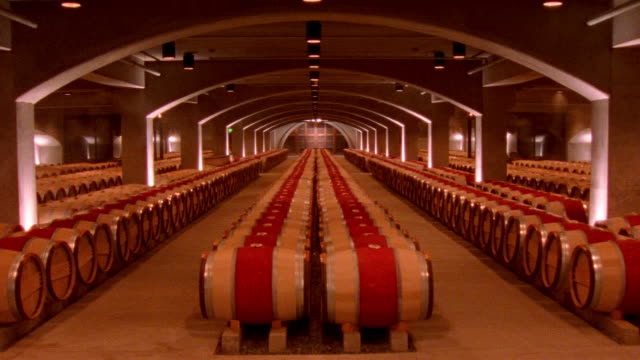 Wide shots rows of casks in cellar at Robert Mondavi Winery/ Napa Valley, California