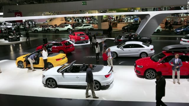 Wide shots visitors stand by automobiles on the Audi AG company stand at the Auto Mobil International automotive trade fair at Leipziger Messe in...