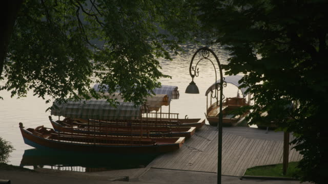 Wide slow motion high angle view of boats and bicycles at waterfront / Bled, Slovenia