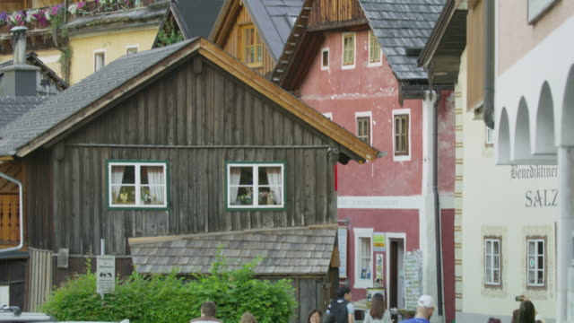Wide slow motion panning shot from sidewalk tilting up to houses / Hallstatt, Austria
