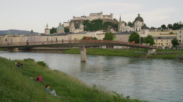 Wide slow motion panning shot of bridge over urban river / Salzburg, Austria