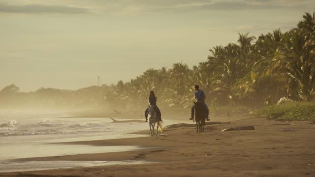 Wide slow motion panning shot of couple riding horseback on beach / Esterillos, Puntarenas, Costa Rica
