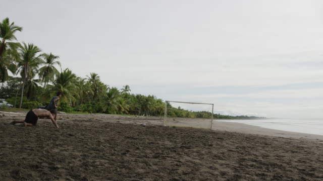 Wide slow motion panning shot of people playing soccer on beach / Esterillos, Puntarenas, Costa Rica