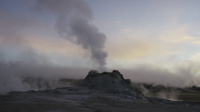 Wide slow motion panning shot of smoking geyser in remote landscape / Yellowstone National Park, Wyoming, United States