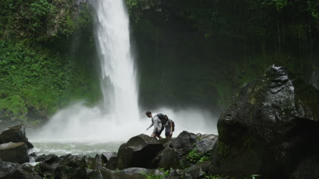 Wide slow motion panning shot of tourists hiking near rain forest waterfall / Arenal, La Fortuna, Costa Rica