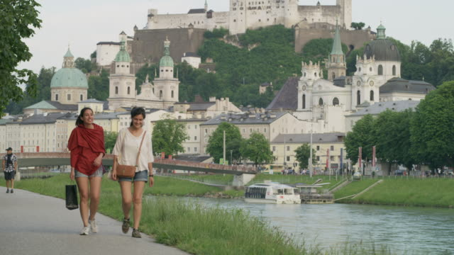 Wide slow motion panning shot of women walking near river / Salzburg, Austria
