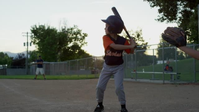 Wide slow motion shot of baseball batter hitting ball and running / American Fork, Utah, United States