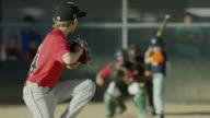 Wide slow motion shot of baseball pitcher throwing strike to batter / American Fork, Utah, United States