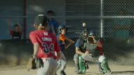 Wide slow motion shot of baseball pitcher throwing strike to batter / American Fork, Utah, United States