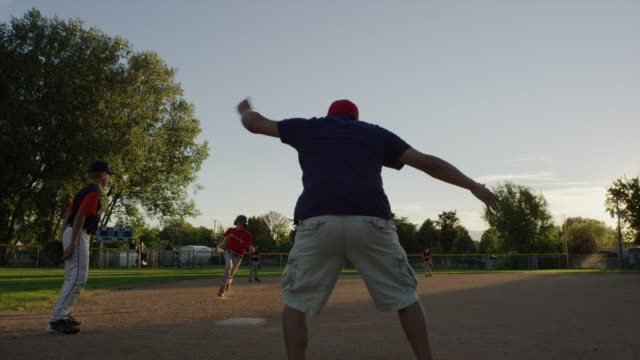 Wide slow motion shot of coach encouraging baseball team / American Fork, Utah, United States