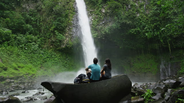 Wide slow motion shot of couple admiring waterfall in rain forest / Arenal, La Fortuna, Costa Rica