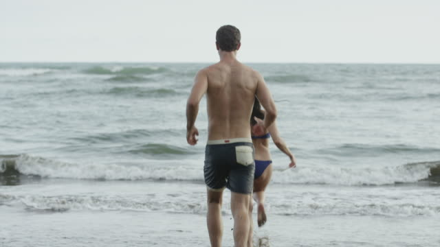 Wide slow motion shot of couple running to ocean on beach / Esterillos, Puntarenas, Costa Rica