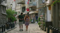 Wide slow motion shot of couple walking on cobblestone street / Veliko Tarnovo, Bulgaria