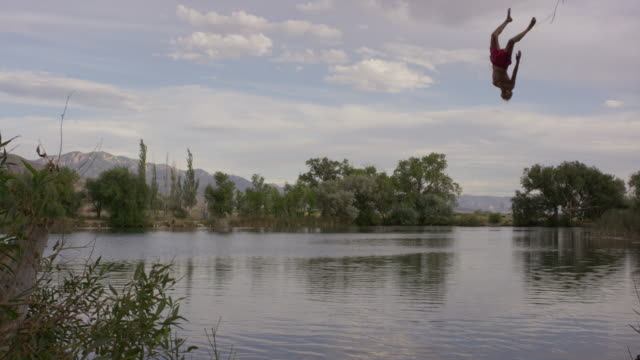 Wide slow motion shot of man swinging into lake / Mona, Utah, United States