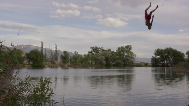 Wide slow motion shot of man swinging into lake / Mona, Utah, United States